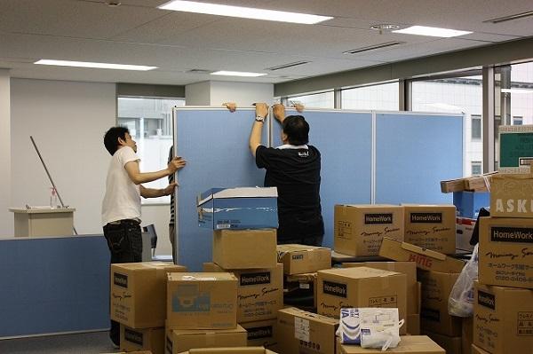 大量の段ボールに囲まれながら作業する社員。会議室用のパーテーションを設置している