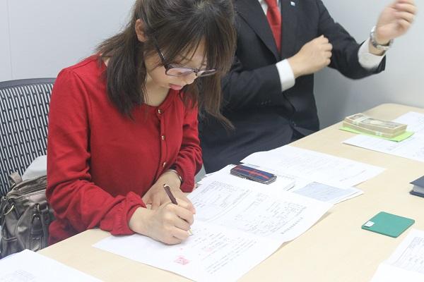 決済日、契約書類を記入する橘みきさん。机の奥には200万円が置いてある